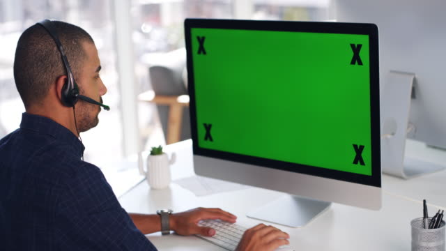 Happy to hear from you 4k video footage of a young man using a computer with a green screen and headset in a modern office call centre videos stock videos & royalty-free footage