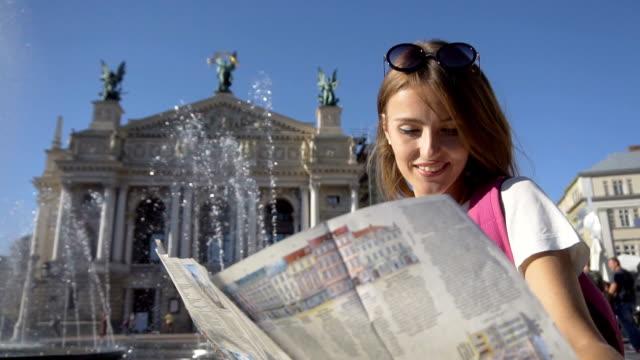 stockvideo's en b-roll-footage met gelukkig toeristische meisje kijken kaart in fontein - wit t shirt