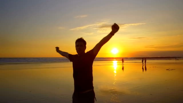 vídeos de stock e filmes b-roll de slow motion: happy tourist man with hands raised spinning on beach at sunset - braços no ar