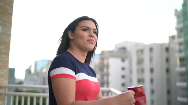 Happy transgender woman looking at view in apartment's porch