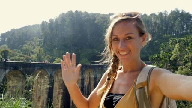 stockvideo's en b-roll-footage met gelukkige reisvrouw die selfie in sri lanka dichtbij oude brug in het gebied van de theeplantage neemt. happy girl video chatten selfie in ella op beroemde bestemming - camelia white