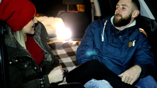 Happy traveler couple sitting in car open trunk video