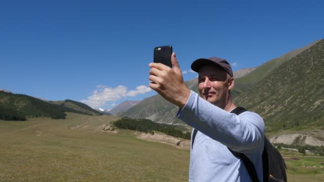stockvideo's en b-roll-footage met gelukkig reiziger schieten video of foto panorama van vallei op telefoon - {{asset.href}}
