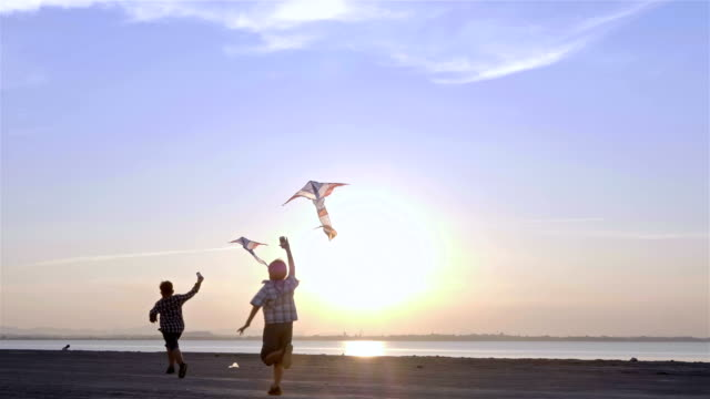 Happy two child boy with a kite running on road and sunlight in summer in nature. Slow Motion