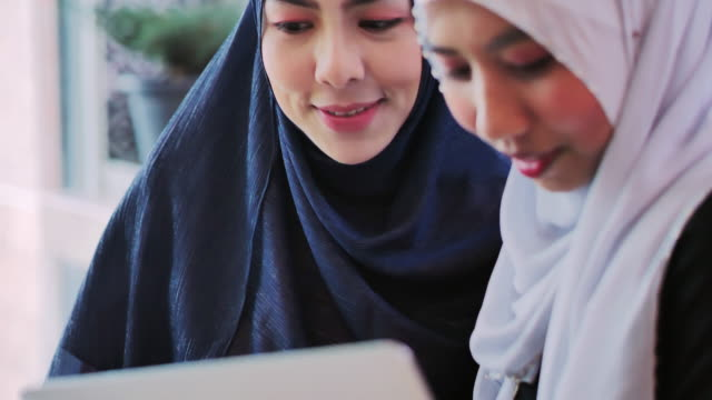 Happy two muslim women shopping online.Young muslim woman in head scarf using laptop in cafe with friends.Arab Youth
