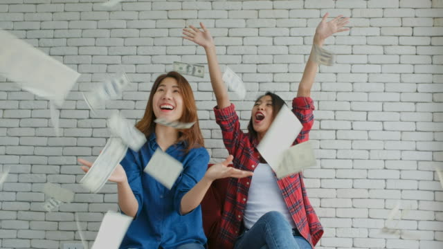 Happy two young asian women holding dollar bills with excitement and throwing up people and business finance
