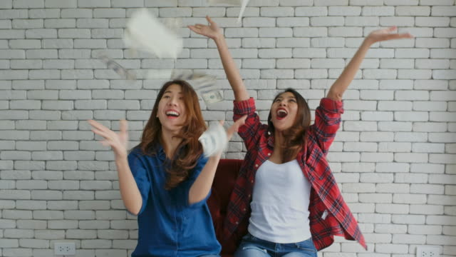 Happy two young asian women holding dollar bills with excitement and throwing up, people and business finance