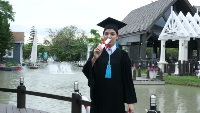 Happy university graduate with a diploma , blowing a kiss Happy university graduate with a diploma , blowing a kiss diploma stock videos & royalty-free footage