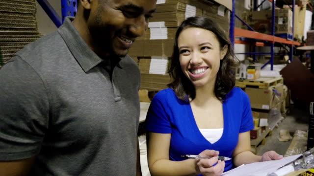 vídeos y material grabado en eventos de stock de voluntarios feliz riendo juntos mientras que las donaciones de clasificación en banco de alimentos - food drive