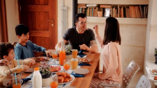 glückliche frau mann fütterung pfannkuchen beim frühstück mit der familie - brunch stock-videos und b-roll-filmmaterial