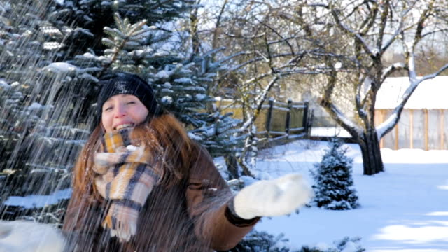Happy winter time. Woman throwing snow in the air in winter holidays. Woman playing with snow video