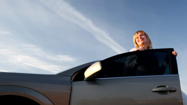Happy woman against the car Happy woman goes out from a car leaving stock videos & royalty-free footage