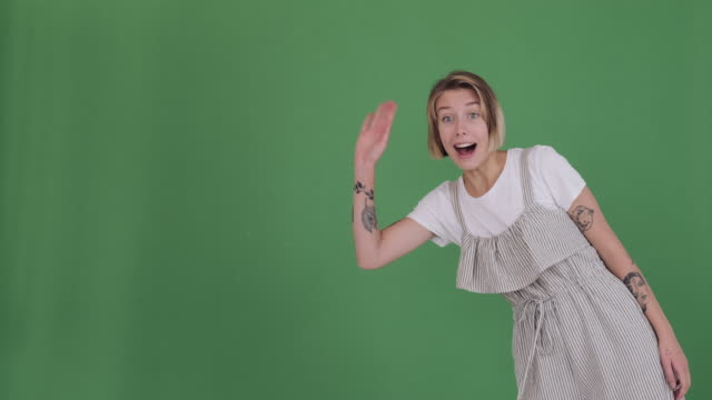 happy woman appearing greeting hello and disappearing on green screen - comparsa video stock e b–roll