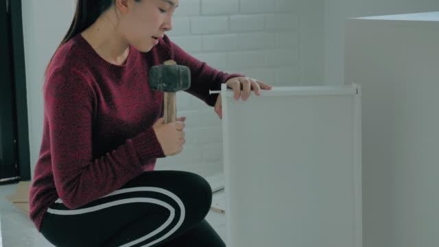 stockvideo's en b-roll-footage met gelukkige vrouw die meubilair assembleert leest instructies en haalt schroef met een boor aan. verhuizen naar new house renovation concept - boekenkast