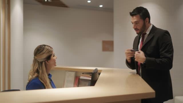 otel resepsiyonist olarak kredi kartı alarak iş yerinde mutlu kadın - hotel reception stok videoları ve detay görüntü çekimi
