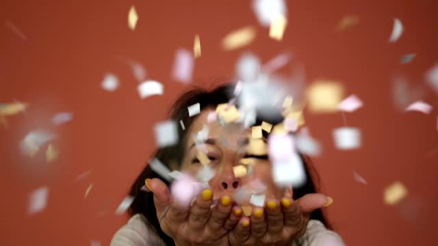 Happy woman blowing confetti,celebrations concept