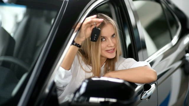 Happy woman buys a new car. She is sitting at the wheel smiling and holding the key