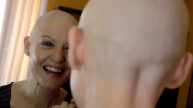 Happy  woman cancer survivor after successful chemotherapy  applying makeup Happy cancer survivor after successful chemotherapy makes up at the mirror: full hd footage cancer patient stock videos & royalty-free footage