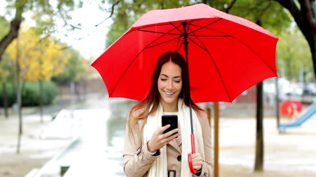 vídeos de stock e filmes b-roll de happy woman checking phone under the rain - guarda chuva