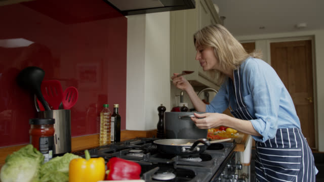 glad kvinna laga middag hemma och smaka på maten medan leende - buljong bildbanksvideor och videomaterial från bakom kulisserna