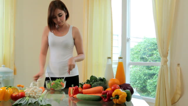 Happy woman cooking vegetables green salad video