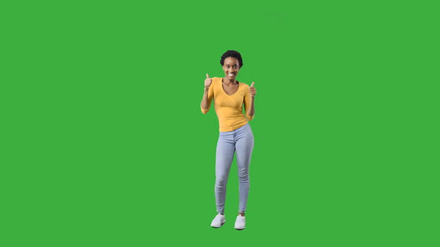 Happy woman dancing and giving thumbs up gesture Happy african american woman dancing and giving thumbs up gesture over green background physical position stock videos & royalty-free footage