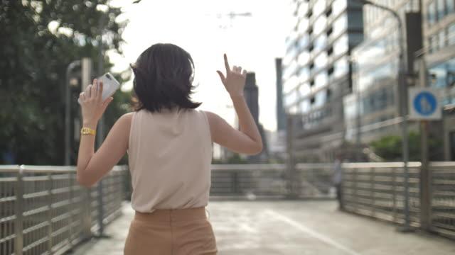 lycklig kvinna dansar och hoppar i galna, roliga danser ute på gatan. - street dance bildbanksvideor och videomaterial från bakom kulisserna