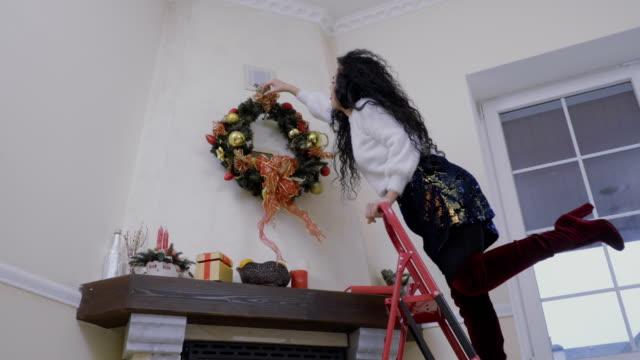 stockvideo's en b-roll-footage met gelukkige vrouw versiert een kroon van kerstmis - christmas tree