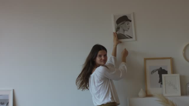 Happy woman decorating house with pictures