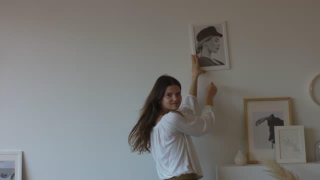 lycklig kvinna dekorera hus med bilder - painting wall bildbanksvideor och videomaterial från bakom kulisserna