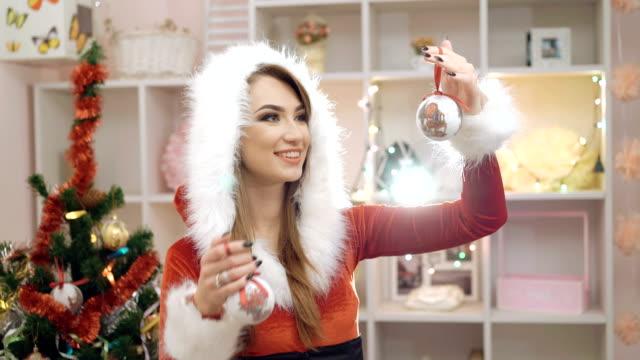 Heureuse femme habillée en costume glamour souriant et à l'aide de Chirstmas jouet en FullHD - Vidéo
