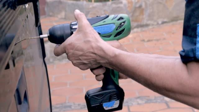 stockvideo's en b-roll-footage met gelukkige vrouw die een gat in de rug van een vrachtwagen met een draadloze boor boor boort - elektrisch gereedschap