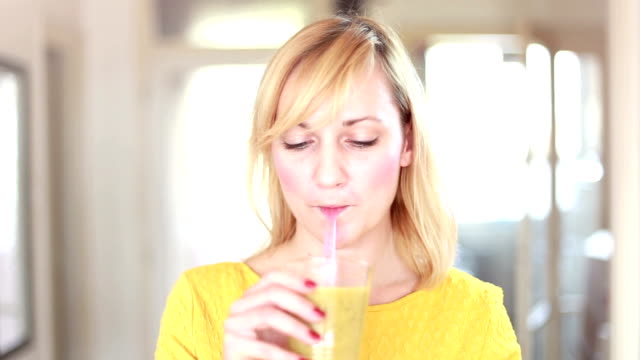 stockvideo's en b-roll-footage met gelukkige vrouw drinken smoothie met rietje - milkshake