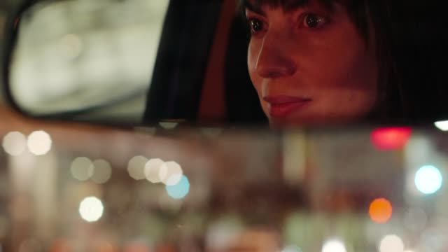 happy woman driving at night. - woman mirror video stock e b–roll