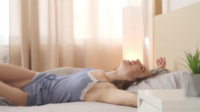 vídeos y material grabado en eventos de stock de mujer feliz dejando en su cama en nightdress - almohada