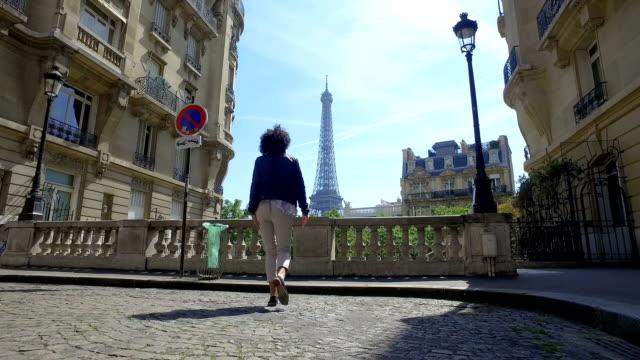 vídeos y material grabado en eventos de stock de la mujer feliz disfruta de la vista panorámica de la torre eiffel de parís caminando y saltando en el pavimento tradicional de la calle y edificios antiguos fachadas - moda parisina