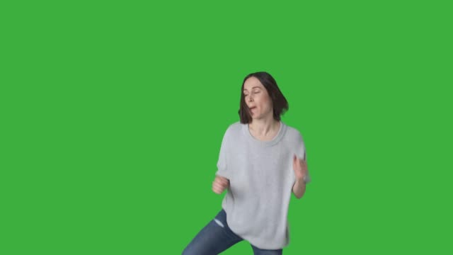 Happy woman enjoying dance over green background