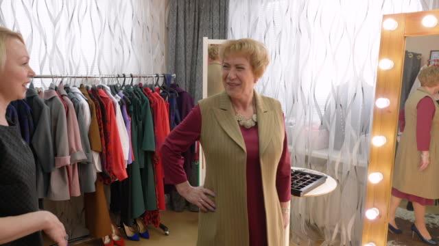 lycklig kvinna mode prova showroom stylist hjälp - skräddare bildbanksvideor och videomaterial från bakom kulisserna