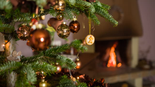 Happy woman finishing decorating christmas tree Cheerful young woman finishing decorating the christmas tree in the comfort of her living room with fireplace burning in the background, panning to the right christmas decoration stock videos & royalty-free footage