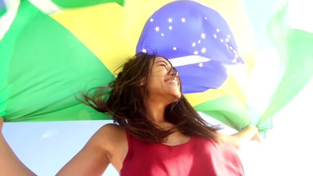 happy woman from brazil with brazilian flag in slow motion - brasilien flagga bildbanksvideor och videomaterial från bakom kulisserna