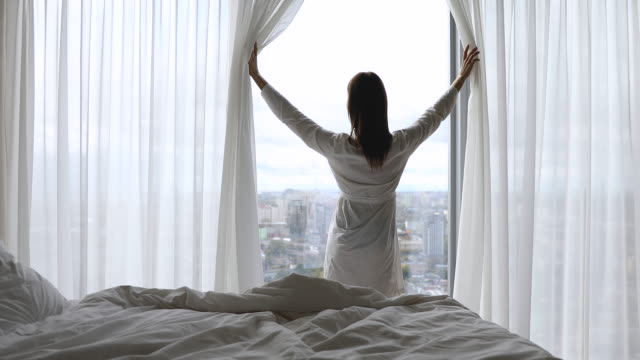 vídeos de stock e filmes b-roll de happy woman get up from bed open window curtain - enjoying wealthy life