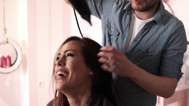 Happy woman getting her hair dried at hair salon. video