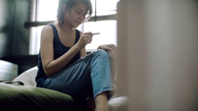 vídeos y material grabado en eventos de stock de mujer feliz con una prueba de embarazo en las manos. - planificación familiar