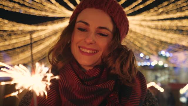 glückliche frau halten brennende wunderkerze. - weihnachtsmarkt stock-videos und b-roll-filmmaterial