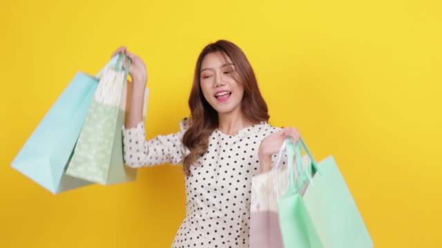 Happy woman holding shopping bags over yellow background