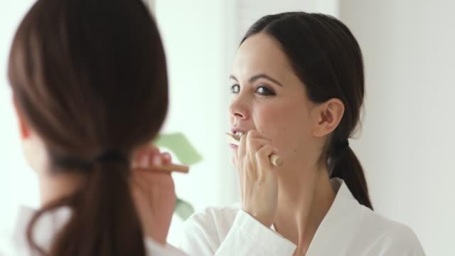 Happy woman holding wooden toothbrush brushing teeth looking in mirror