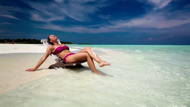Happy woman in chair on the sea beach in sunny day with feet in water video
