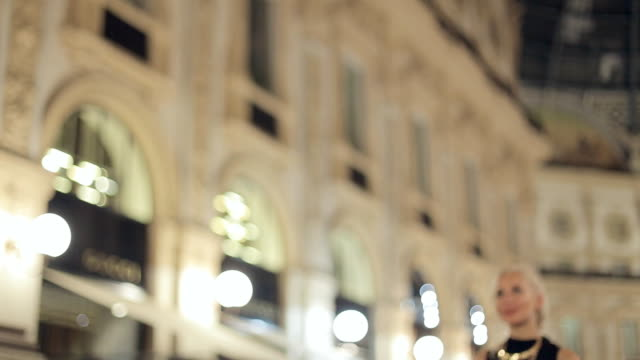 Happy woman in one of the world's oldest shopping malls, in Milan at night video