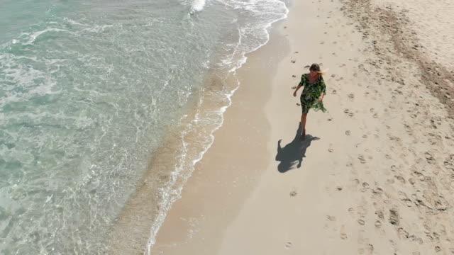 lycklig kvinna i sarong promenader på stranden - sarong bildbanksvideor och videomaterial från bakom kulisserna