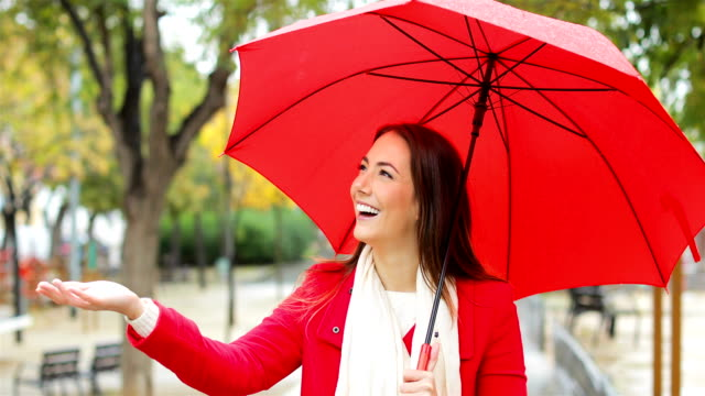 Happy woman in red walking under the rain